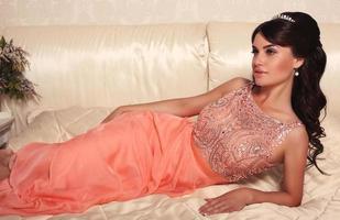 Hermosa novia con cabello oscuro en elegante vestido coral
