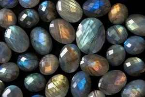 Dark beautiful gemstones background: many faceted colorful labradorite gems.