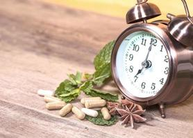 Time to eat Organic Herb capsule medicine with mint leaves photo