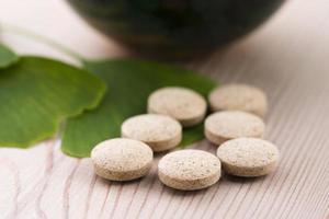 hojas de ginkgo biloba en mortero y pastillas foto