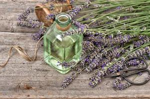 Herbal lavender oil with fresh flowers bouquet on wooden background