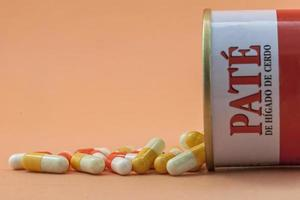 Some pills go out of a canister of pate photo