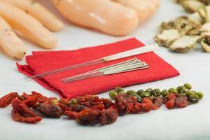 close uo Chinese acupuncture needles on red cloth with meridian