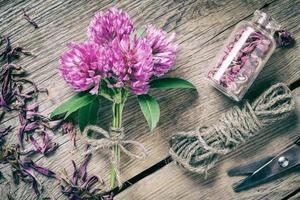 Bunch of clover, bottle with dried herb and jute rope