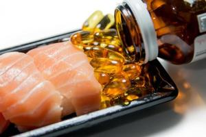 Salmon sushi served with fish oil pills photo