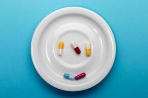 Five colorful capsules on a plate