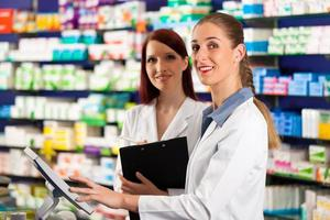 Pharmacist with assistant in pharmacy photo