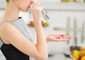 closeup em jovem dona de casa comendo comprimidos e bebendo água