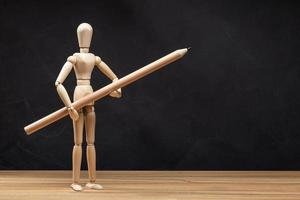 Wooden mannequin holding a pencil photo