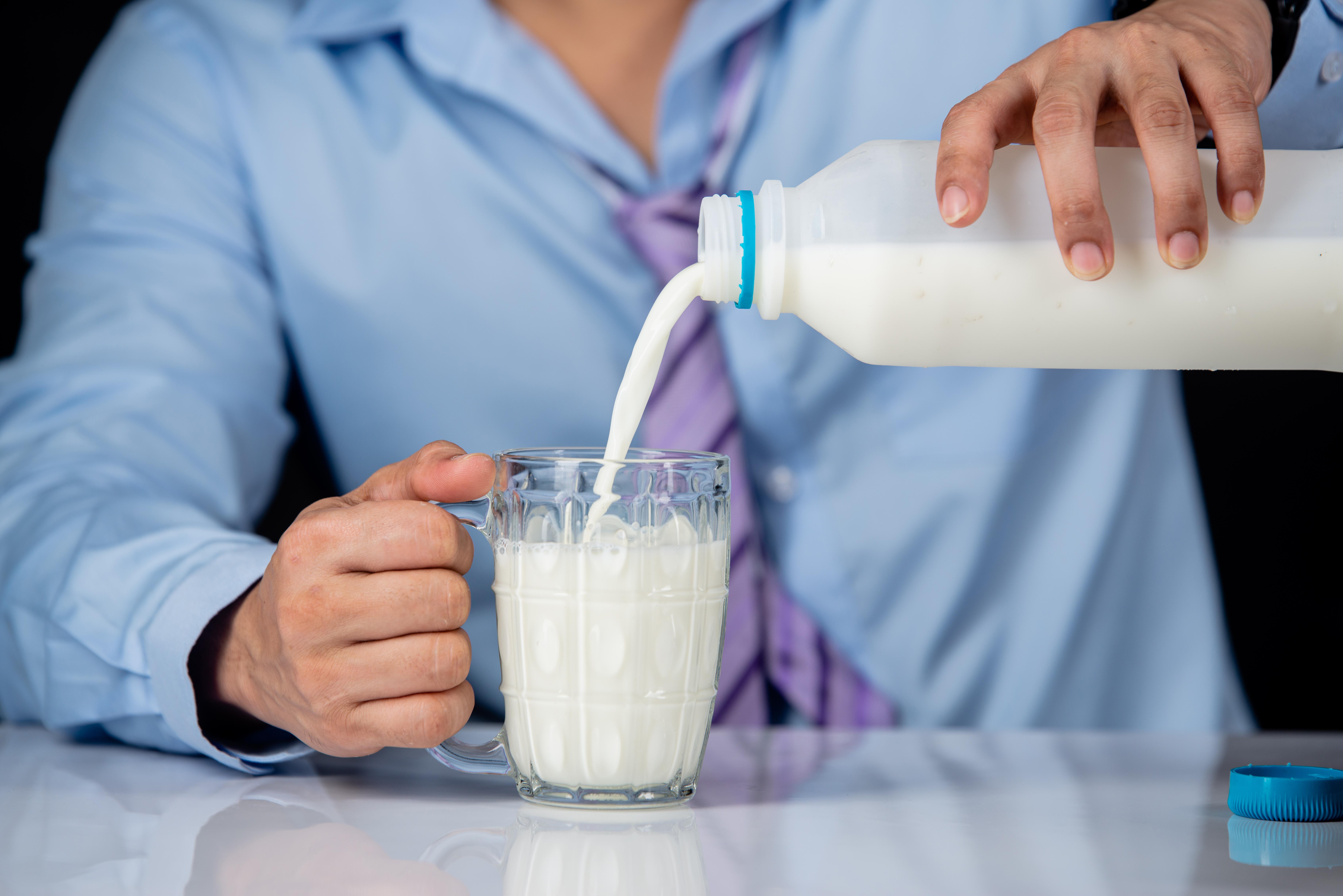 hombre vertiendo leche