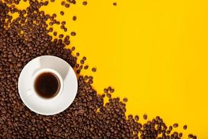Coffee cup and roasted beans on yellow background
