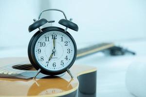 Retro alarm clock on a guitar photo