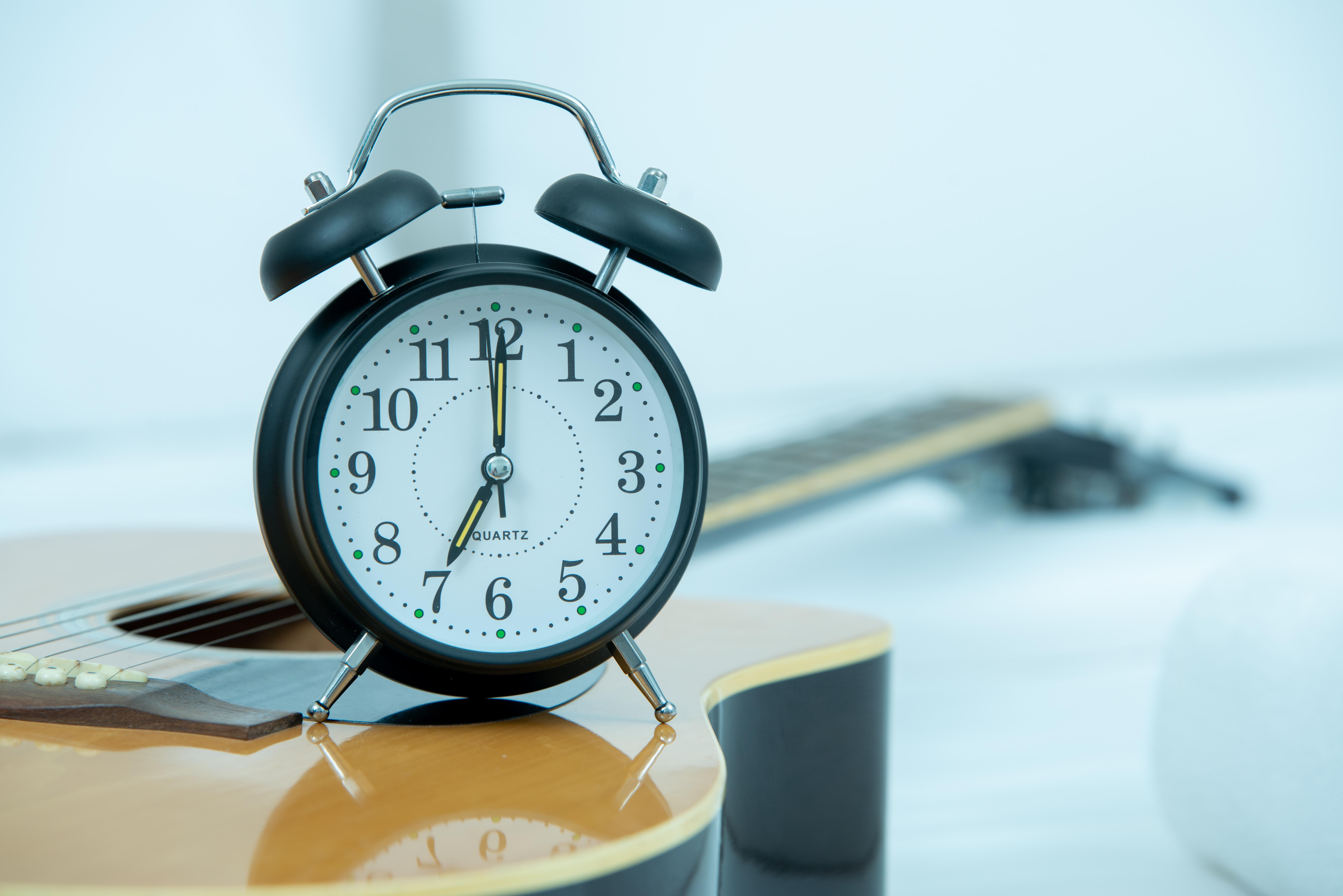 reloj despertador retro en una guitarra