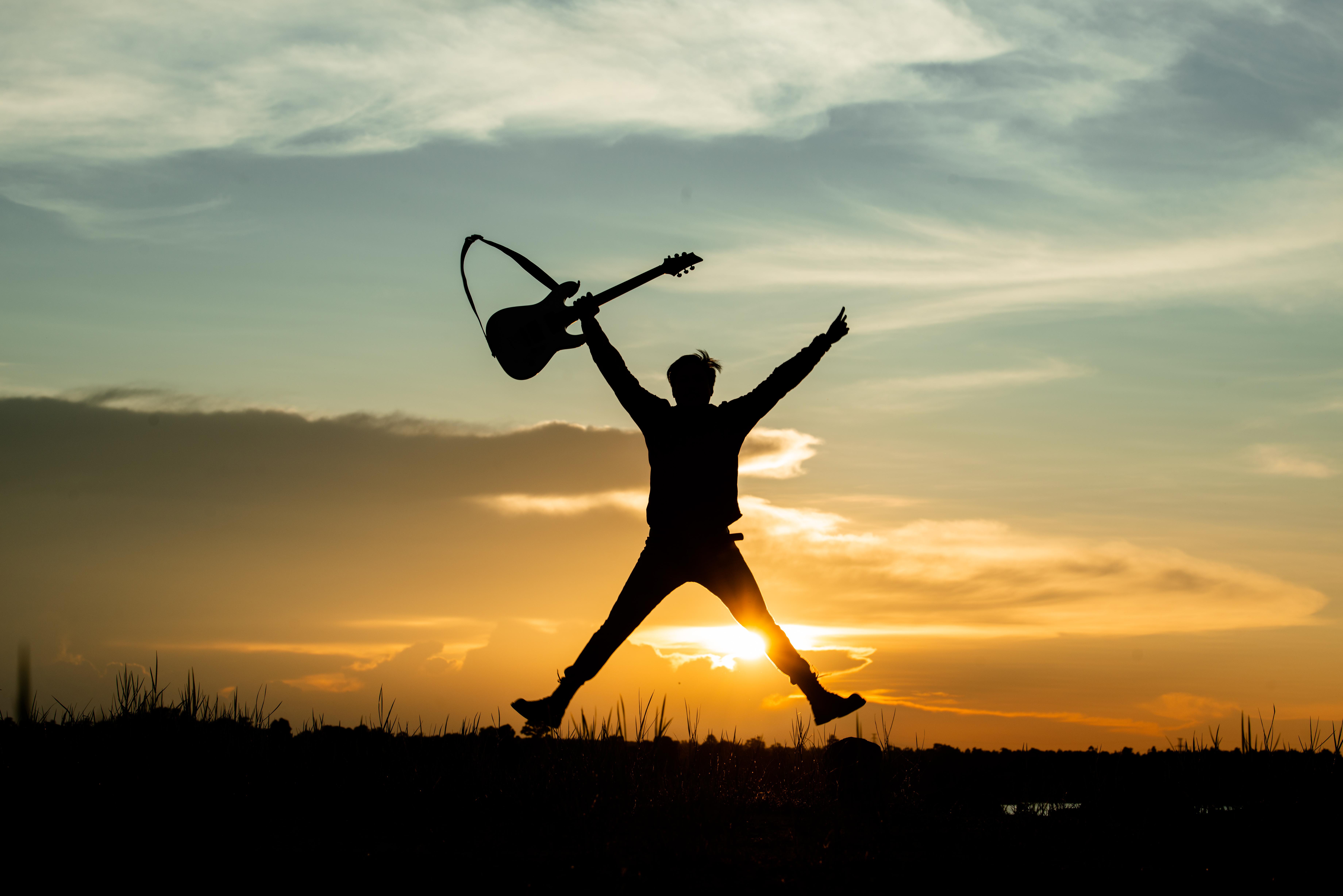 pessoa pulando com sua guitarra