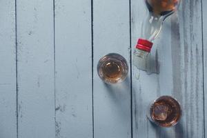 bodegón con vasos y una botella de alcohol foto
