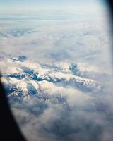 mountain ranges covered in clouds from an airplane window