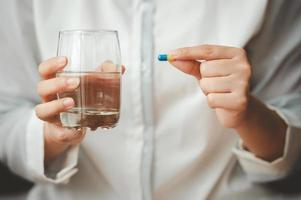 Hand holding capsule pill and glass of water