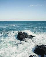 Ocean waves crashing on rocks under a blue sky