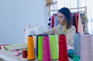 Fashion designer working on sewing machine photo