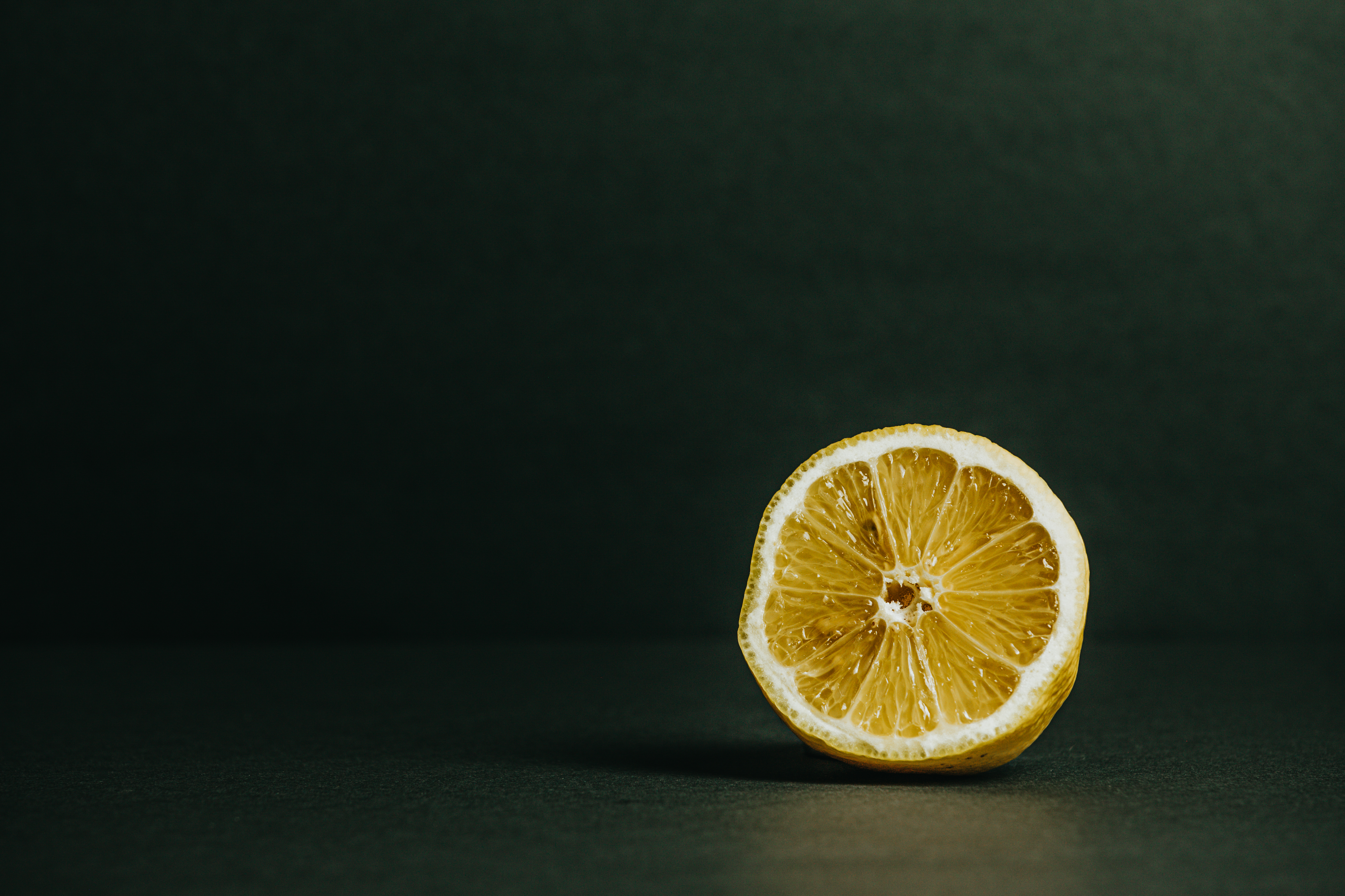 Half of a lemon on a green background