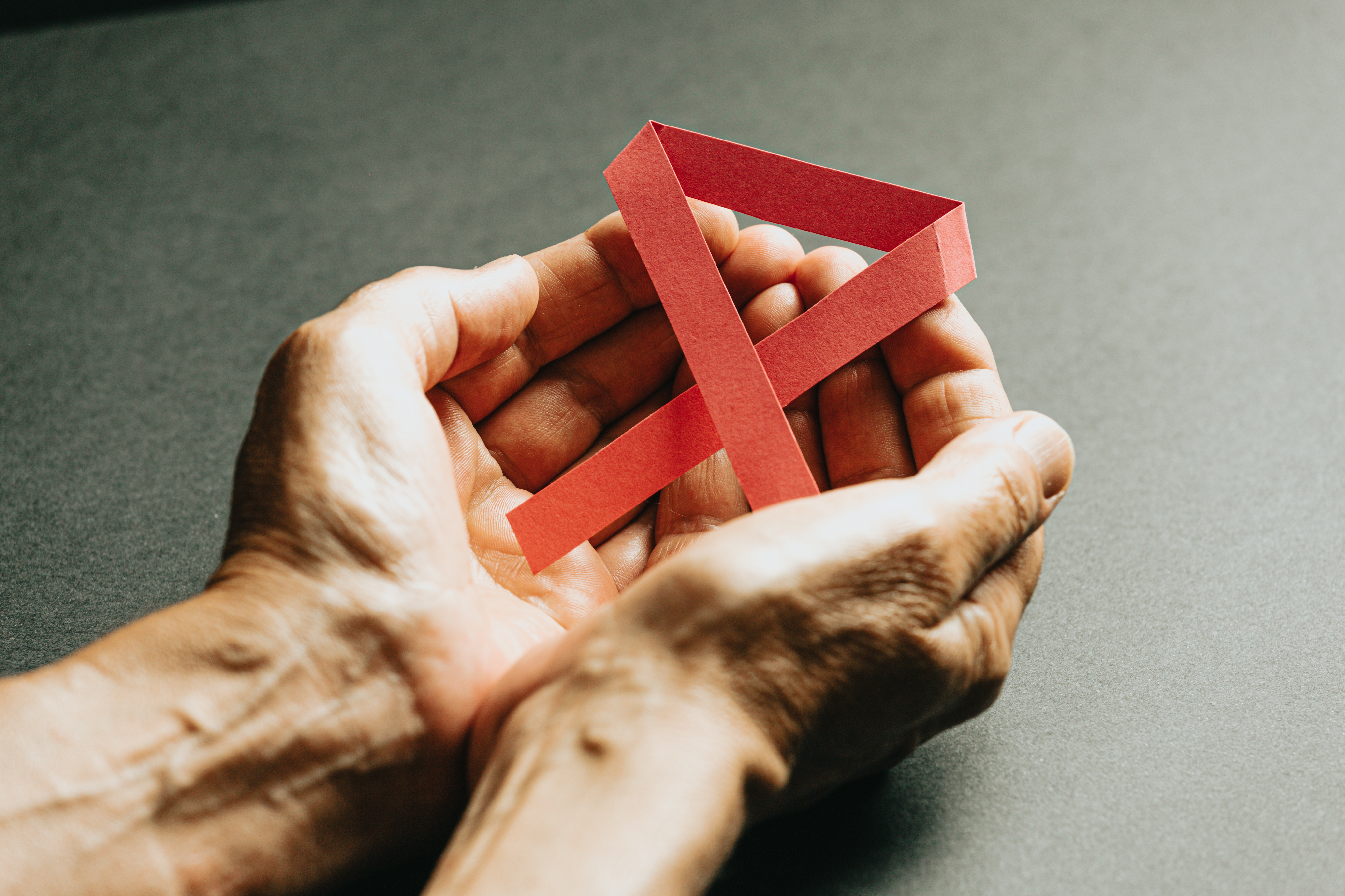 manos sosteniendo una cinta rosa