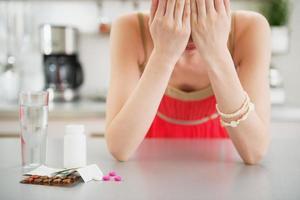 sentirse mal chica y pastillas en la mesa foto