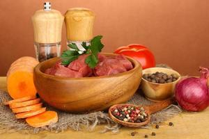 Carne de res cruda marinada con hierbas y especias en la mesa foto