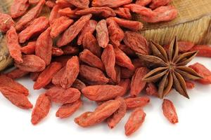 Goji berries on oak wood with star anise isolated