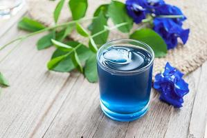 Fresh butterfly pea juice and butterfly pea flower on wooden