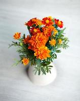Marigolds flowers in vase on grey background