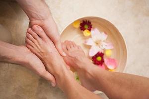 pedicurista lavando los pies de un cliente foto