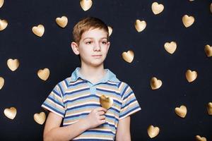 Boy holding gold heart on dark background photo