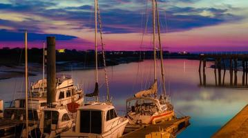 Sail boats docked on marine in beautiful sunset photo