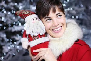 Christmas woman smiling with gift, Santa Claus toy,
