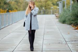 mujer de cabello rubio caminando por la calle y sonríe foto