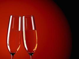 Dos copas de champán en una mesa con fondo de colores