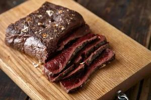 Closeup of sliced medium rare cooked whale meat stake wooden photo