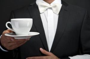 camarero en traje sosteniendo la taza de café foto