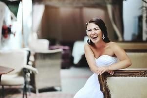 Happy bride sitting in restaurant. photo