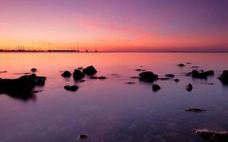 puesta de sol sobre barcos con rocas en primer plano foto