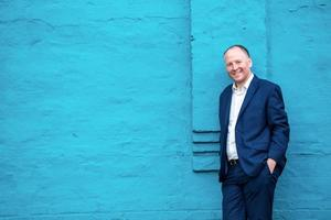 Positive businessman leaning on turquoise wall