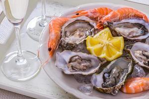 Garnished oysters shell, jumbo shrimp with lemon on ice