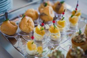 Beautifully decorated catering banquet table with different food snacks appetizers