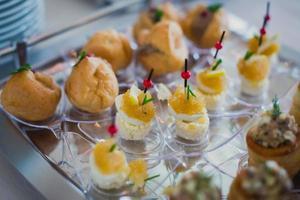 mesa de banquete de catering bellamente decorada con diferentes aperitivos de comida foto