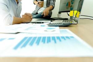 Close-up de documentos en el escritorio con trabajadores en segundo plano.