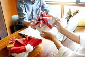 Coworkers exchanging Christmas presents in office