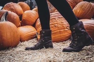Person standing near pumpkins