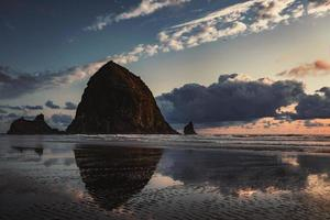 Reflection of monolith Haystack Rock in Oregon photo