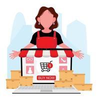 Woman standing behind laptop wearing apron