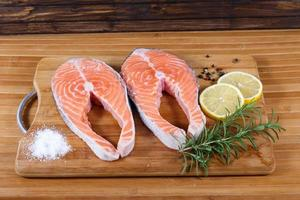Raw salmon with lemon on wooden table photo